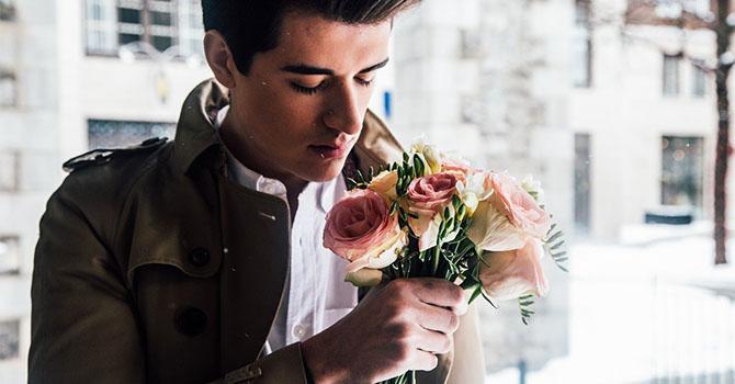 バラを持った美しい男性
